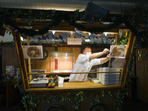 Cook Sascha Richter puts up photos of the menu (Markus Schreiber/AP)