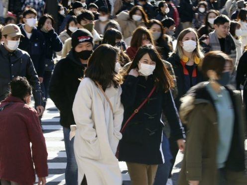 People wearing face masks to help curb the spread of the coronavirus walk around the scrambled intersection at the Shibuya shopping district in Tokyo (Kyodo News via AP)