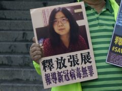 A pro-democracy activist holds placards with the picture of Chinese citizen journalist Zhang Zhan (AP/Kin Cheung)