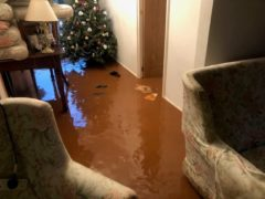 Flood water surrounds a Christmas tree at Helddwyn James's home in Sully, South Wales (Craig James/PA)