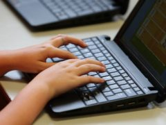 A pupil using a laptop during lesson time (PA)