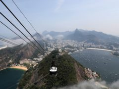 A cable car makes its way up to the top of Sugarloaf mountain from Urca Hill, in Rio de Janeiro, Brazil (Andrew Matthews/PA)