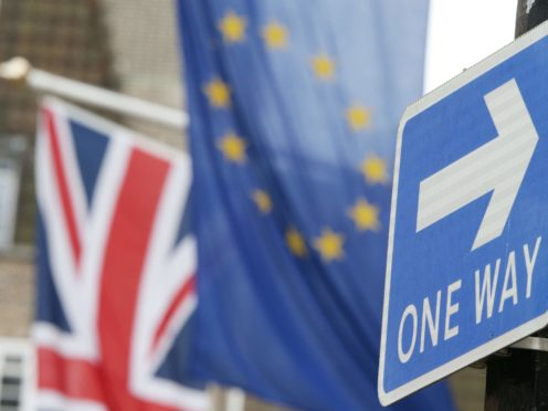 A road traffic sign is in front of the Union Jack and the European Union flag hanging outside Europe House in Smith Square, London (Yui Mok/PA)