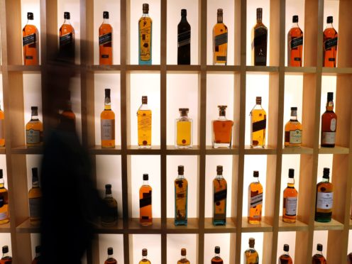 A person walks past Diageo-owned whiskies on the whisky wall at its headquarters in Edinburgh (Andrew Milligan/PA)