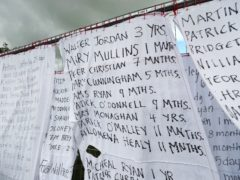 Hotel bed sheets with the names of hundreds of dead children draped on the gates of a mass burial site at Tuam, Co Galway (Niall Carson/PA)