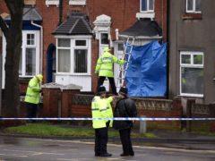 Police staff cover broken windows of a property on Pensnett Road, Brierley Hill, West Midlands (Matthew Cooper/PA)