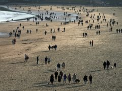 People walking on a beach (Owen Humphreys/PA)