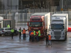 Lorry drivers and officials talk at the DEARA site near Belfast Port (Liam McBurney/PA)