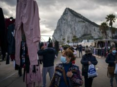 Backdropped by the Gibraltar rock, people wearing face masks walk along the stalls of a weekly market at the Spanish city of La Linea (Emilio Morenatti/AP)