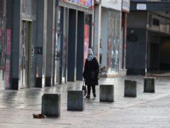A woman walks through an empty Glasgow city centre (Andrew Milligan/PA)