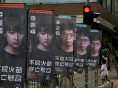 Banners of pro-democracy candidate Joshua Wong, wearing glasses, are displayed outside a subway station in Hong Kong (Vincent Yu/AP)