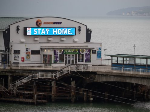 A 'Stay Home' sign is displayed on Bournemouth pier in Dorset (Andrew Matthews/PA)