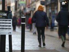 People make their way past a Government coronavirus Tier 4 sign saying 'Stay at Home' on the High street in Winchester, Hampshire (Andrew Matthews/PA)
