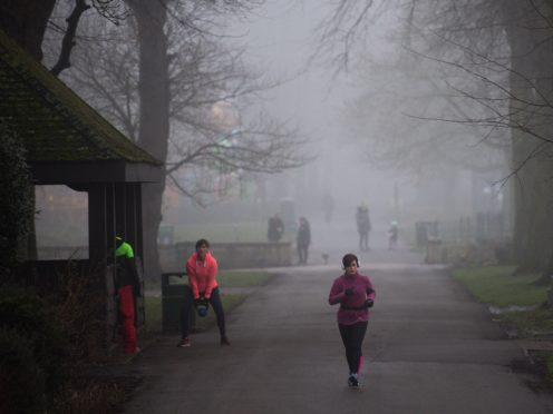 People exercise in a cold and foggy St Nicholas' Park in Warwick (PA)