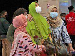 Relatives of passengers arrive at a crisis centre (AP)