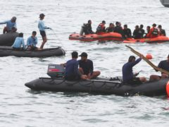 Rescuers carry debris found in the waters around the site where a Sriwijaya Air passenger jet crashed on Saturday (Achmad Ibrahim/AP)