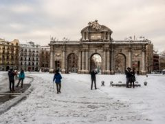 People walk through snow in Madrid's Puerta de Alcala square (Manu Fernandez/AP)