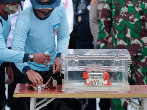 Indonesian navy personnel handle a box containing the flight data recorder recovered from the crash site of the Sriwijaya Air flight SJ-182 (Dita Alangkara/AP)