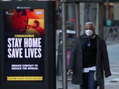 A member of the public walks passed a coronavirus related advert on a bus stop in Glasgow (Andrew Milligan/PA)