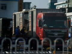 Workers wearing face masks to help curb the spread of coronavirus load frozen foods to a lorry in Beijing (Andy Wong/PA)