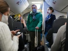 Alexei Navalny and his wife Yulia board the plane at Berlin Brandenburg Airport in Germany (Mstyslav Chernov/AP)