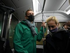 Alexei Navalny, centre, and his wife Yulia travel on an airport bus as they arrive at Sheremetyevo airport, outside Moscow, on Sunday (Mstyslav Chernov/AP)