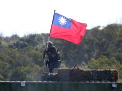 A soldier holds a Taiwan national flag during a military exercise in Hsinchu County, northern Taiwan (Chiang Ying-ying/AP)