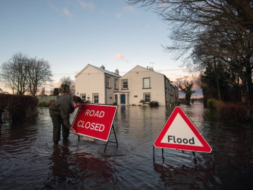 Gabrielle Burns-Smith erects a road closed sign on Warrington Lane on the outskirts of Lymm in Cheshire (Joe Giddens/PA)