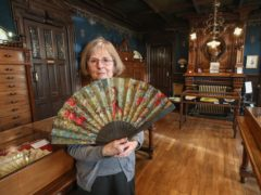 Anne Hoguet, 74, fan maker and director of the hand fan-making museum, poses with a a wood roasted hand fan representing the falcon hunt, gouache painting on paper dated from 1880 in Paris (Michel Euler/AP)