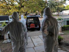 Sri Lankan municipal workers wait as they prepare for the cremation of a Covid-19 victim (Eranga Jayawardena/AP)