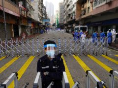 A police officer stands guard at the Yau Ma Tei area in Hong Kong (Vincent Yu/AP)