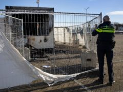 A police officer takes pictures of a coronavirus testing facility in a Dutch fishing village which was set alight (Peter Dejong/AP)