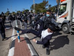 Israeli police officers clash with ultra-Orthodox Jews in Ashdod, Israel, Sunday, Jan. 24, 2021. Ultra-Orthodox demonstrators clashed with Israeli police officers dispatched to close schools in Jerusalem and Ashdod that had opened in violation of coronavirus lockdown rules, on Sunday. (AP Photo/Oded Balilty)
