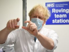 Prime Minister Boris Johnson holds a vial of the Oxford/Astrazeneca coronavirus vaccine during a visit to Barnet FC's ground at The Hive, north London, which is being used as a coronavirus vaccination centre. Picture date: Monday January 25, 2021.