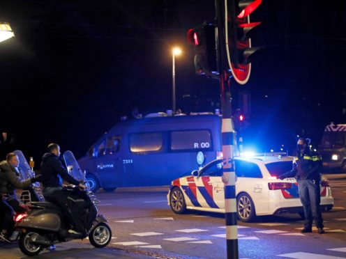 A police officer speaks to youths on scooters at a roadblock in Amsterdam during a nationwide curfew (Peter Dejong/AP)