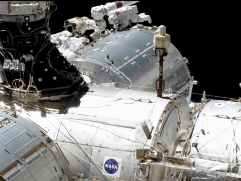 Astronauts Mike Hopkins, centre right, and Victor Glover, centre left, work outside the International Space Station's European lab (NASA via AP)