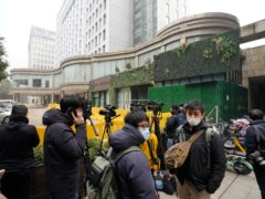 Journalists gather outside the hotel where a team of experts from the World Health Organization are quarantined in Wuhan in centra China's Hubei province on Thursday, Jan. 28, 2021. A World Health Organization team has emerged from quarantine in the Chinese city of Wuhan to start field work in a fact-finding mission on the origins of the virus that caused the COVID-19 pandemic.(AP Photo/Ng Han Guan)