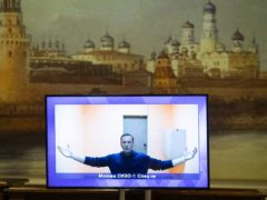 Russian opposition leader Alexei Navalny appears on a TV screen during a live session with the court during a hearing of his appeal in Moscow (Pavel Golovkin/AP)