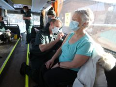 Paramedic Andrew Parker gives the vaccine to Elizabeth Robertson inside the coach (Andrew Milligan/PA)