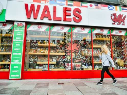 A woman wears a face covering as she walks past a shop in Cardiff (Ben Birchall/PA)