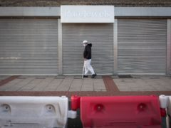 A man walks along Green Street in east London, a normally busy shopping street which is now a road of boarded up shops (Stefan Rousseau/PA)