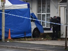 Police search the grounds of a nearby property after sealing off Queens Cross, Dudley (PA)