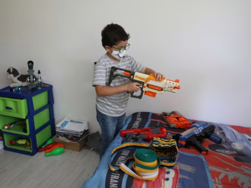 Francisco Vera, well-known in Colombia for his environmental campaigns and defence of children's rights, plays with his toys at home in Villeta, Colombia (Fernando Vergara/AP)