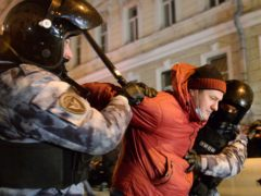 Police officers detain a Navalny supporter at the Red Square in Moscow, Russia, Tuesday, Feb. 2, 2021. A Moscow court has ordered Russian opposition leader Alexei Navalny to prison for more than 2 1/2 years on charges that he violated the terms of his probation while he was recuperating in Germany from nerve-agent poisoning. Navalny, who is the most prominent critic of President Vladimir Putin, had earlier denounced the proceedings as a vain attempt by the Kremlin to scare millions of Russians into submission. (AP Photo/Denis Kaminev)