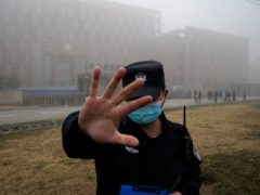 A security guard moves journalists away from the Wuhan Institute of Virology after a World Health Organisation team arrived for a field visit in Wuhan on Wednesday (Ng Han Guan/AP)