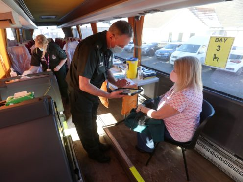 A vaccine is given inside a converted holiday coach in Culloden, in the Highlands (Andrew Milligan/PA)
