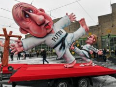 A political carnival float depicting Russia's President Vladimir Putin fighting with opposition leader Alexei Navalny is rolled out to be shown in the streets of Duesseldorf, Germany (Martin Meissner/AP)