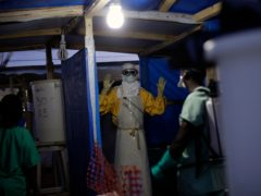 A health worker is sprayed as he leaves the contaminated zone at the Ebola treatment centre in Gueckedou, Guinea (Jerome Dela/AP)