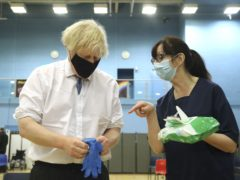 Prime Minister Boris Johnson struggled to put on a pair of medical gloves during a visit to the vaccination centre at Cwmbran Stadium in Cwmbran, South Wales (Geoff Caddick/PA)