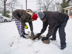 Patricia Broadway, left, and Leon Morris put the cover back after shutting the water off in Ms Broadway's home in the East Dallas area (Juan Figueroa/The Dallas Morning News via AP)